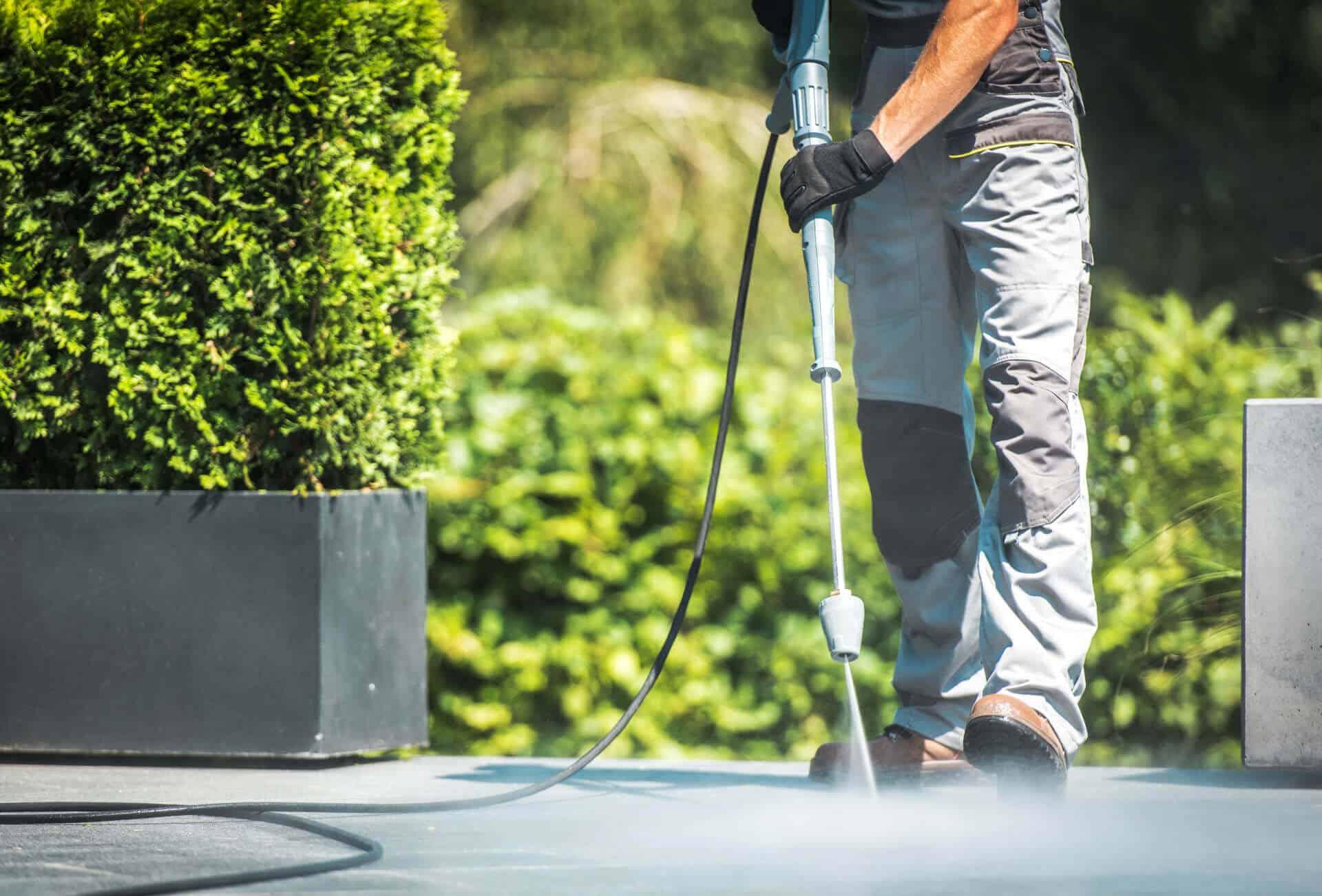 Man pressure cleaning floor