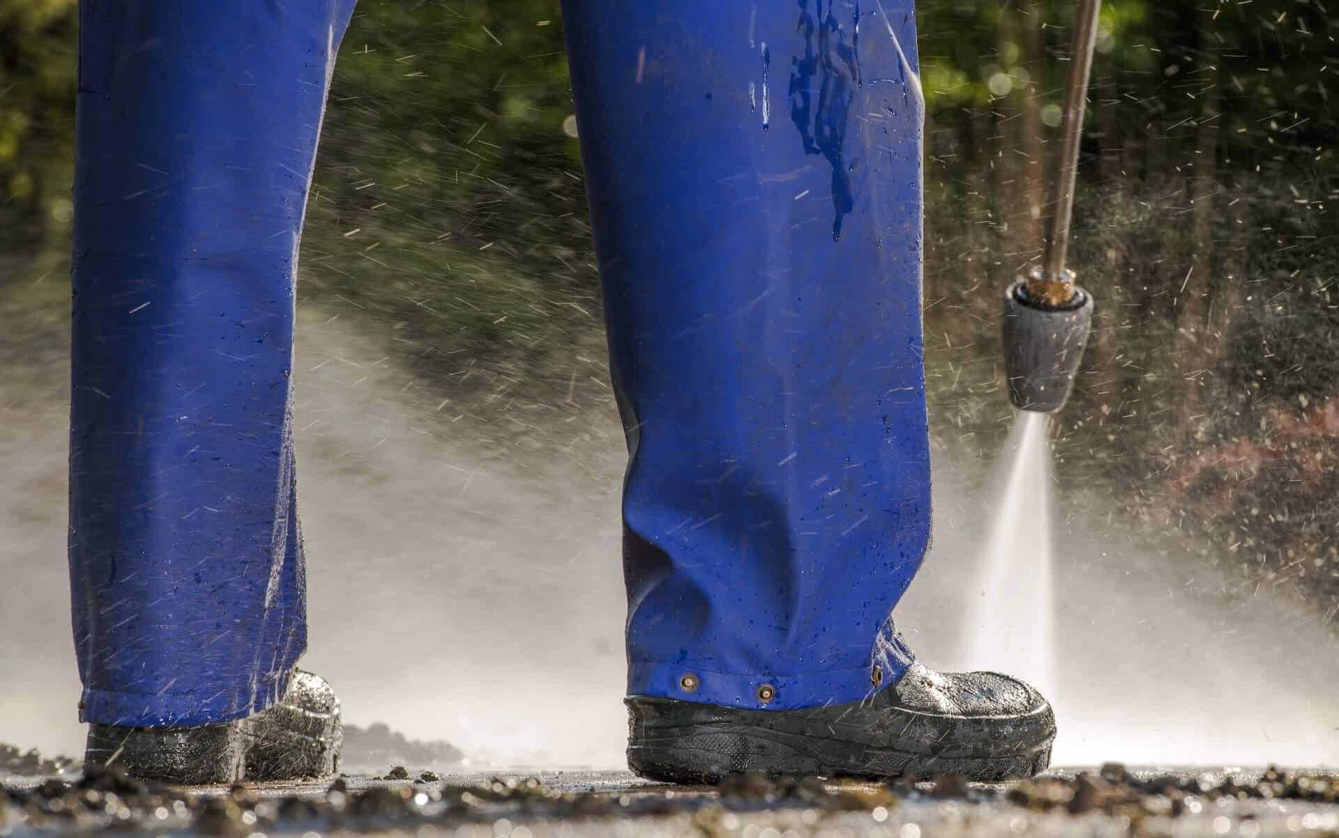 man pressure cleaning ground