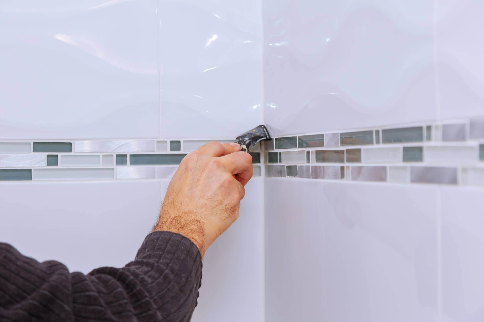 man working on bathroom tiles