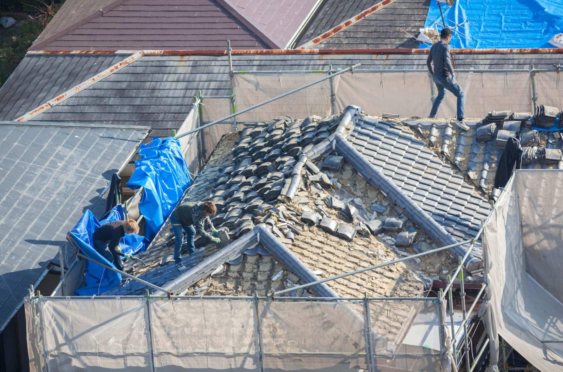 three men fixing roof tiles